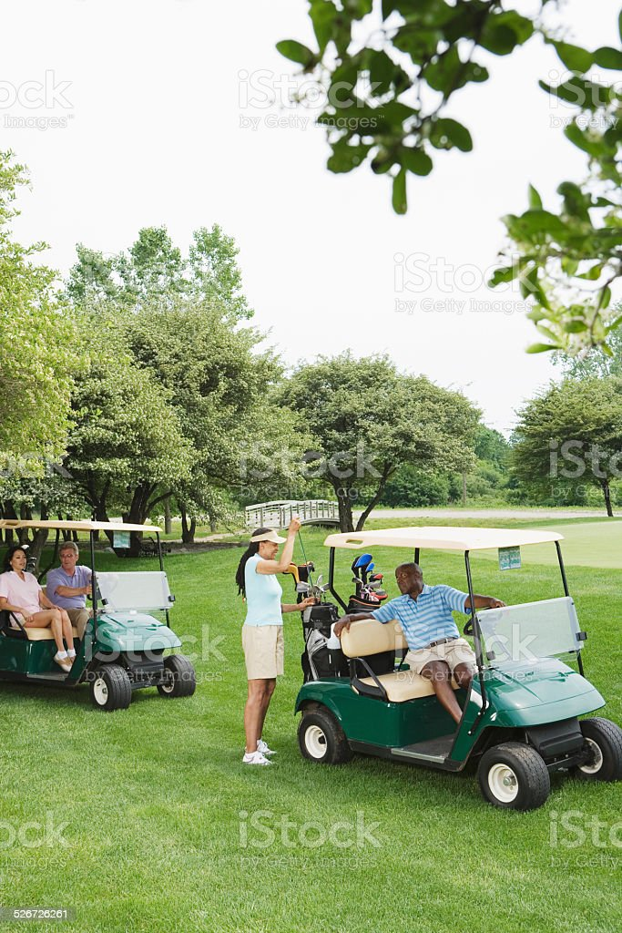 Two couples in golf buggies on golf course stock photo