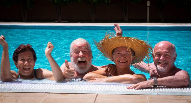 zwei seniorenpaare lachen und genießen gemeinsam das schwimmbad. helles sonnenlicht und transparentes wasser. großes lächeln und glück - senior bilder wasser stock-fotos und bilder