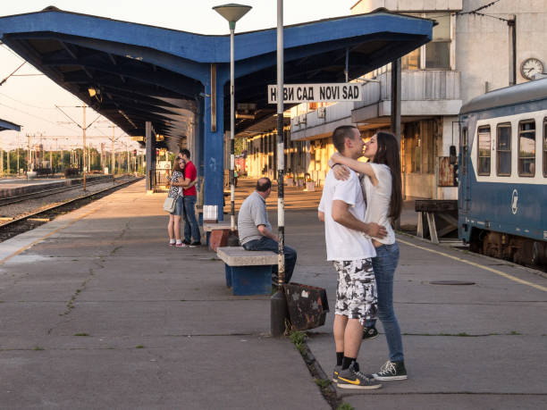 Two couples of white caucasian male and females kissing in Novi Sad train station waiting for the train that will separate them stock photo