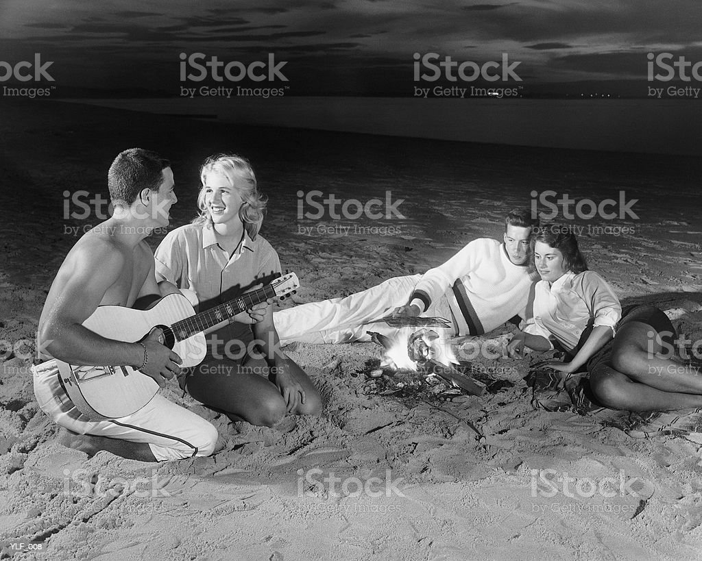 Two couples on beach sitting around campfire royalty-free stock photo