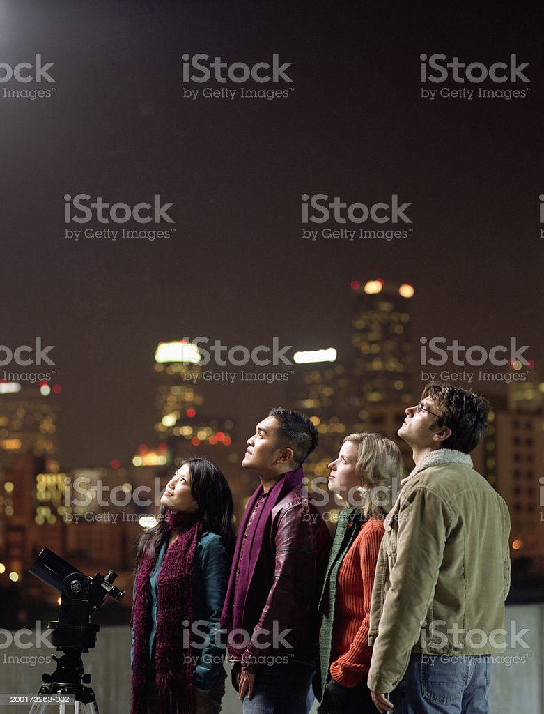 Two couples on rooftop, looking upwards at night sky Los Angeles, California, USA 25-29 Years Stock Photo