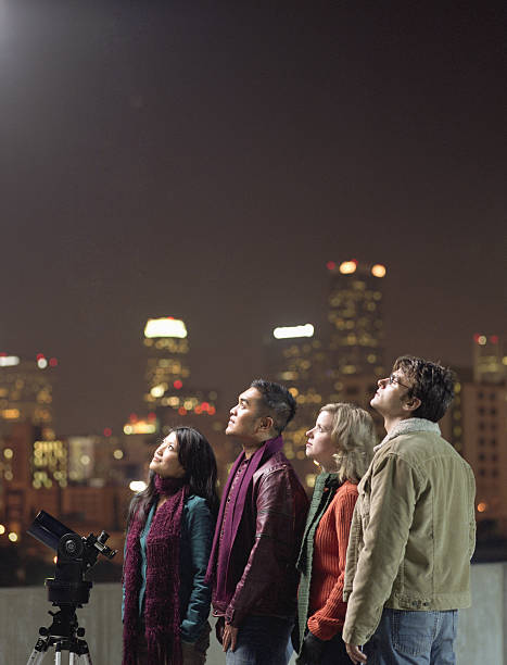 Two couples on rooftop, looking upwards at night sky stock photo