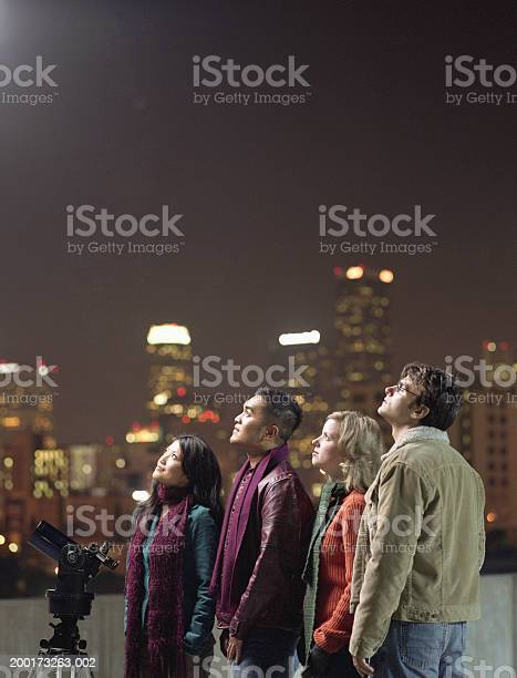 Two Couples On Rooftop Looking Upwards At Night Sky Stock Photo - Download Image Now
