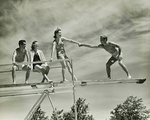 Two couples on springboard, (B&W), low angle view stock photo