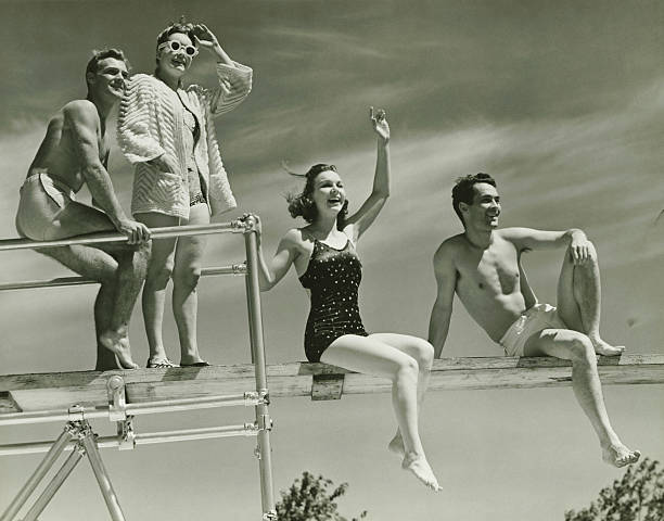 two couples on springboard, (b&w), low angle view - vintage stock photos and pictures