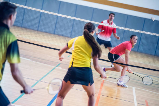 Two couples playing badminton Rear view of two couples playing badminton against each other on an indoor court. badminton stock pictures, royalty-free photos & images
