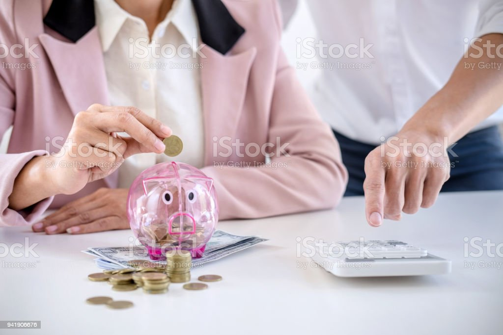 Two couples putting coins into piggy bank, writing to report and using calculator to analysis business investment strategy with income of money coin and dollar, financial concept stock photo