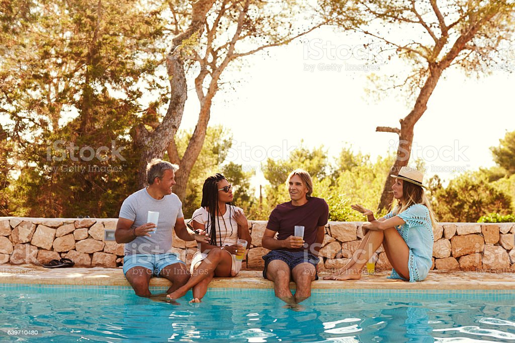 Two couples sit at poolside talking, front view royalty-free stock photo