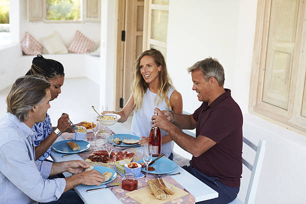 two couples sitting down for dinner at a table on - paletten terrasse stock-fotos und bilder