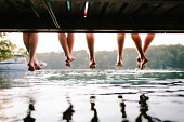 Legs of two couples sitting on a jetty hanging down to the water. Shot from under the jetty at sunset.