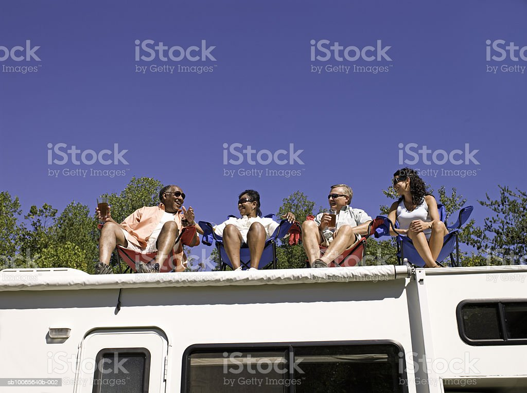 Two couples sitting on roof of motorhome, low angle view Lizenzfreies stock-foto