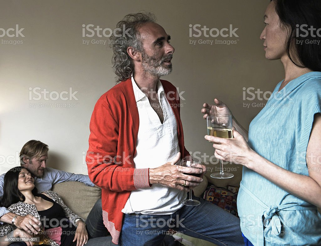 Two couples spending time together in living room royalty free stockfoto