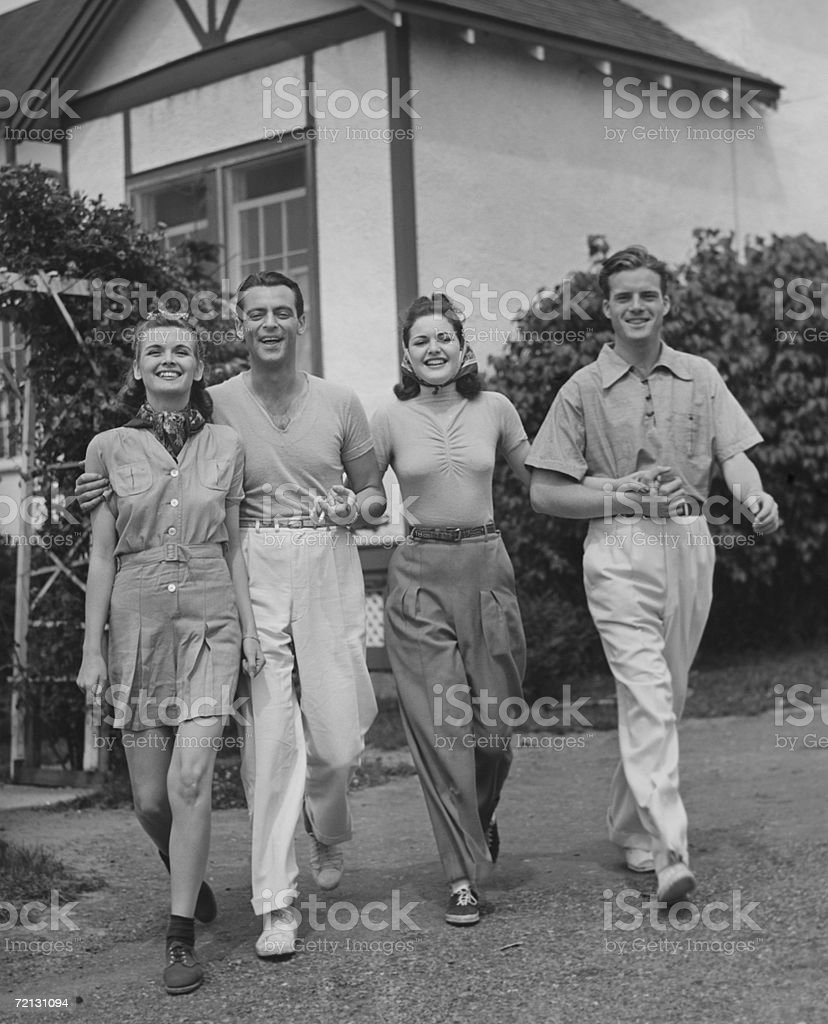 Two couples walking on lawn in front of house (B&W) stock photo