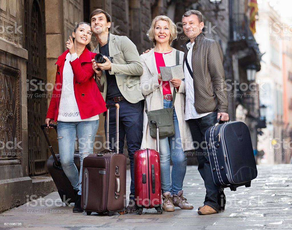 Two couples with luggage search for sights on map stock photo