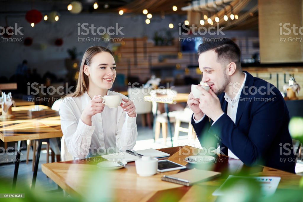 Two coworkers, businessman and businesswoman having coffee together. Business people talking friendly at cafe royalty-free stock photo