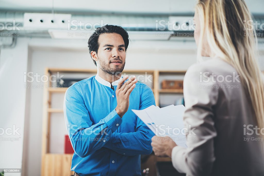 Two coworkers discussing business project in modern office.Successful confident stock photo