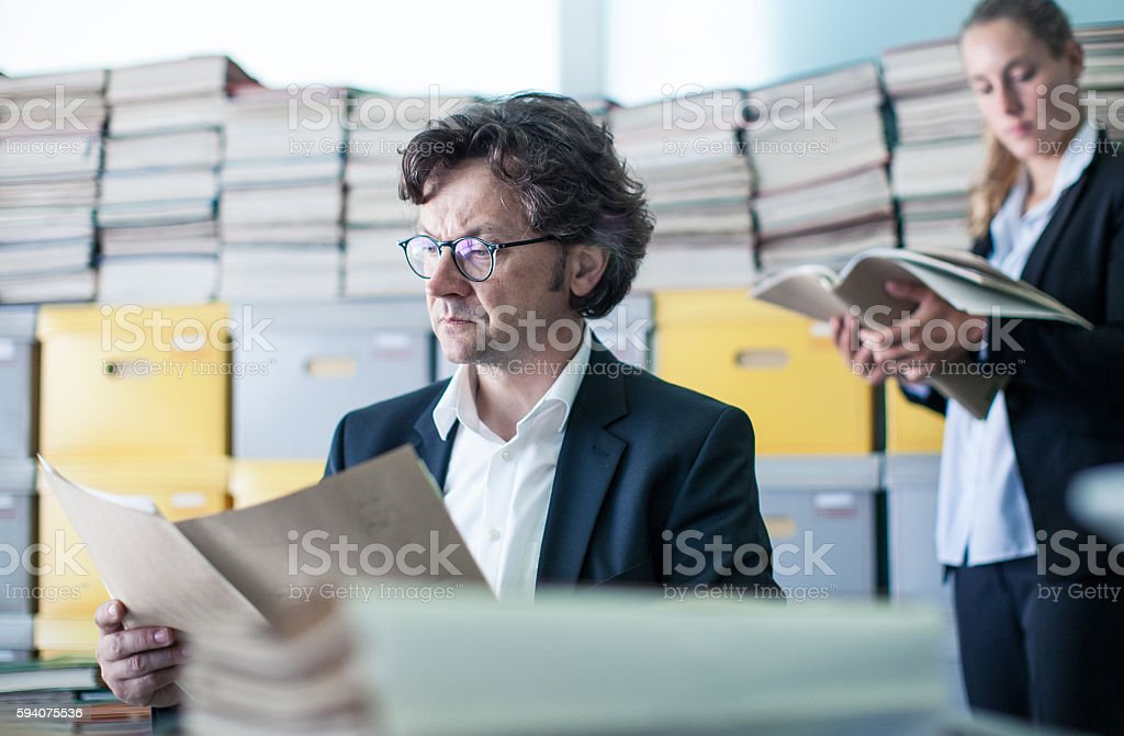 Two Coworkers Looking at Paperwork in the Office stock photo