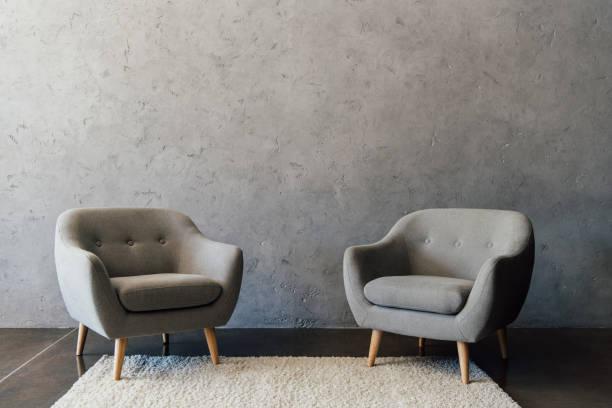 Dos sillones gris acogedoras de pie sobre la alfombra blanca en habitación vacía - foto de stock