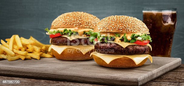 Two craft beef burgers on wooden table isolated on blue background. A glass with a drink stands in the background with a french fries