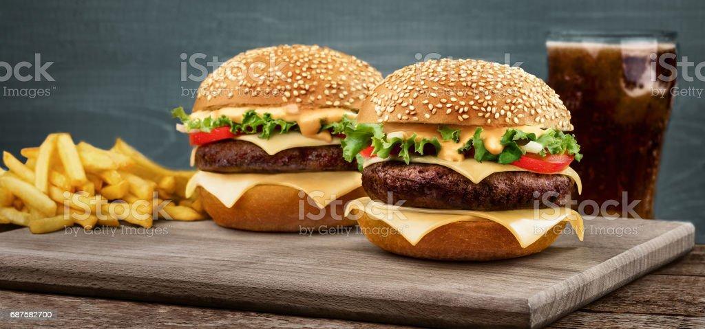 Twee ambachtelijke rundvlees hamburgers op houten tafel op blauwe achtergrond foto