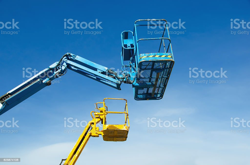 Two crane's baskets against clear sky stock photo