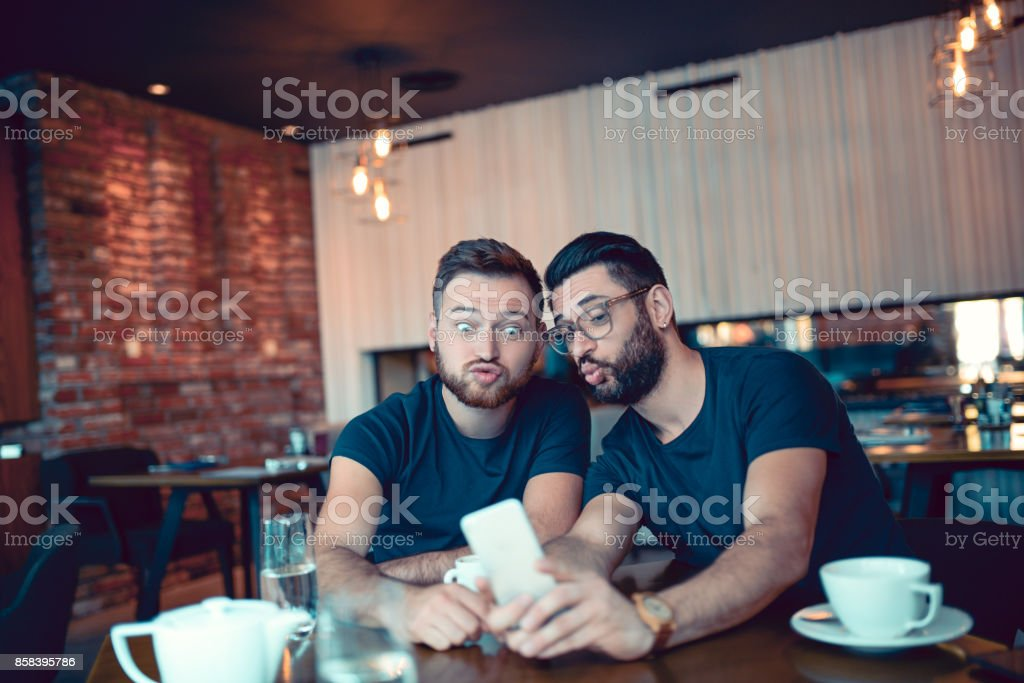 Two Crazy Frieds Making Selfie with Duck Face in Cafe Restaurant stock photo