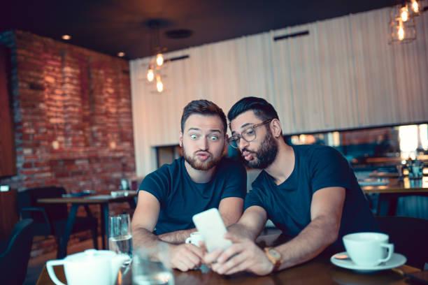 zwei verrückte frieds selfie mit ente machen gesicht im cafe-restaurant - emoticon hug stock-fotos und bilder