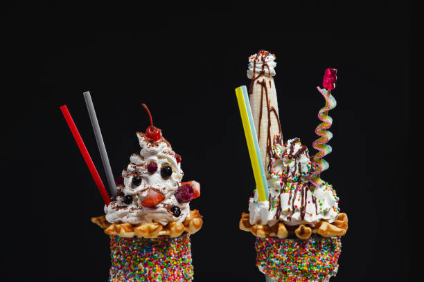 Two crazy giant milkshakes against black background stock photo
