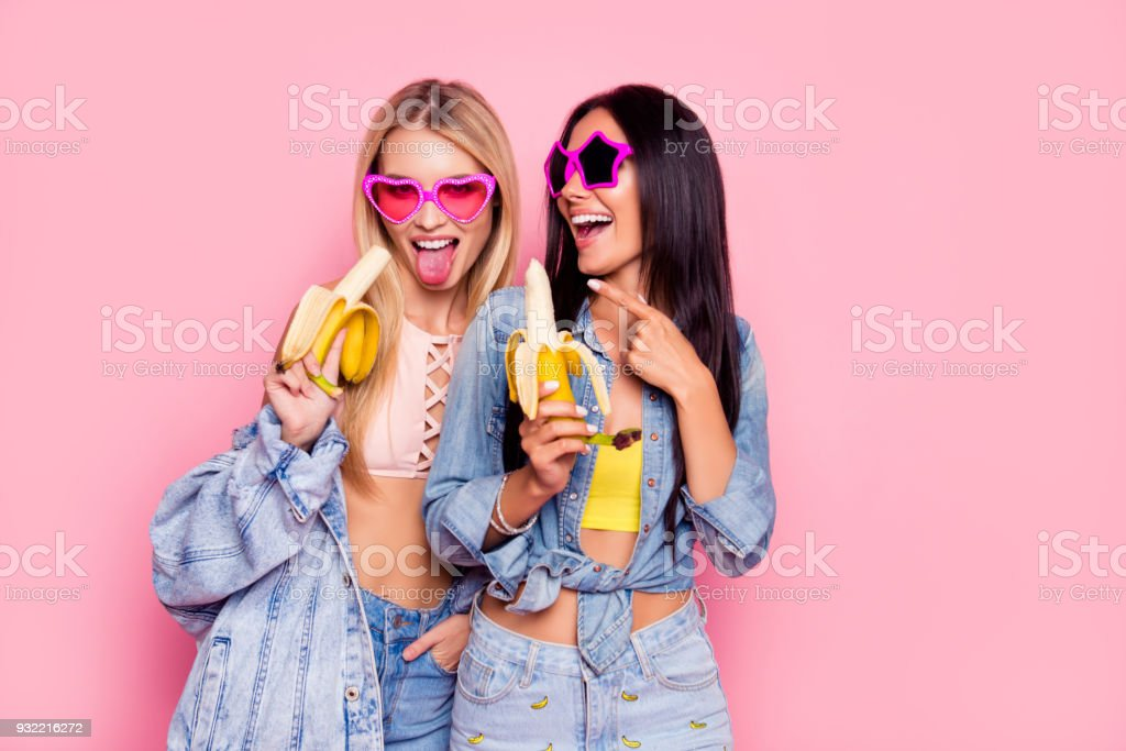 Two crazy mad friends are fooling around! Beautiful attractive funny joyful cheerful women clothed in trendy outfit and star heart glasses are showing tongue and laughing isolated on pink background stock photo