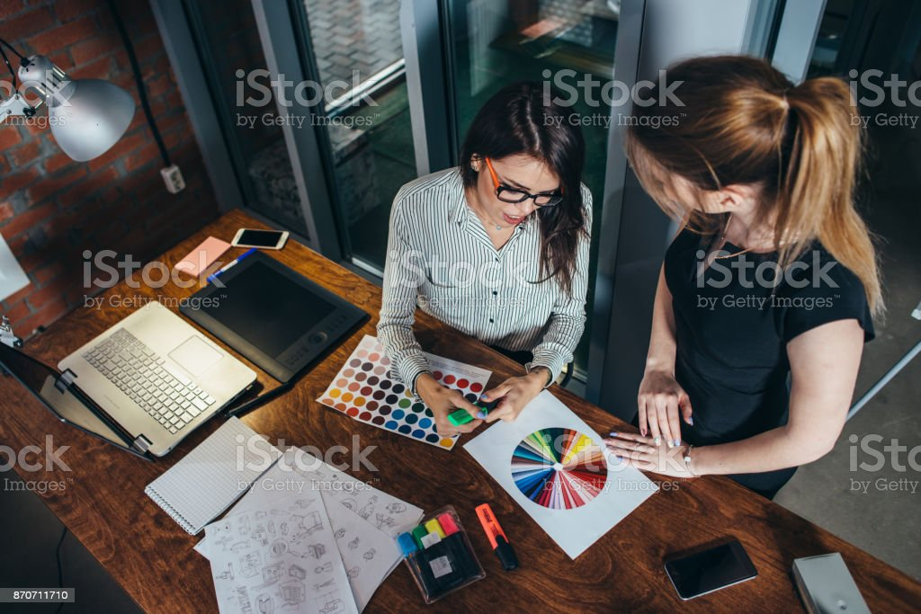 Two creative female designers choosing colors working with colour palette in the office stock photo