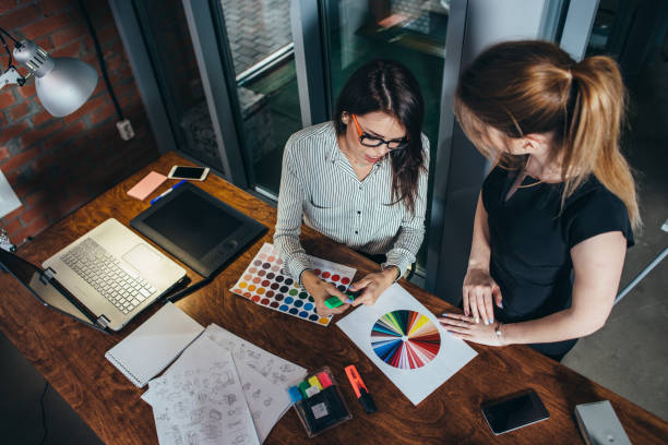 two creative female designers choosing colors working with colour palette in the office - advertisement stock photos and pictures