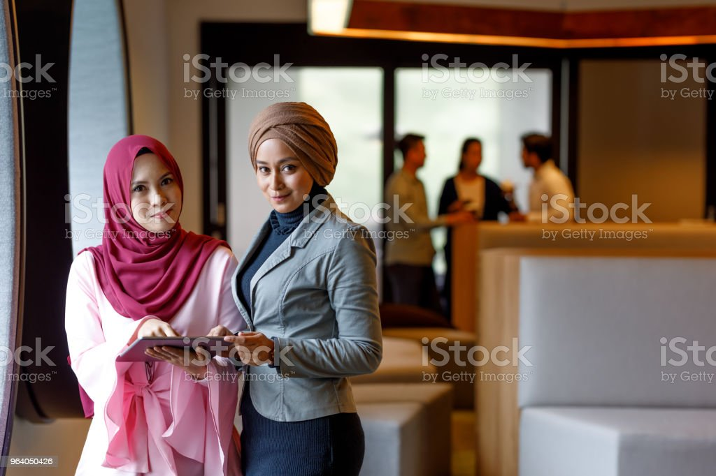 Two Creative Muslim Women Discussing Ideas stock photo