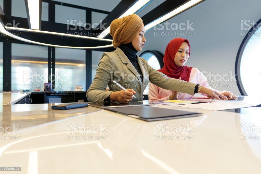 アイデアを議論する 2 つの創造的なイスラム教徒の女性 - あこがれのロイヤリティフリーストックフォト