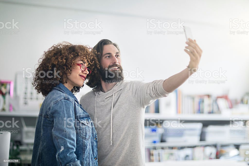 Two creative people making a selfie at the office stock photo