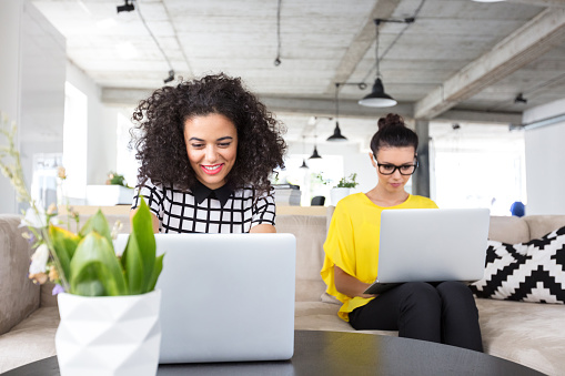 Two Creative Professionals Working On Their Laptop Stock Photo - Download Image Now