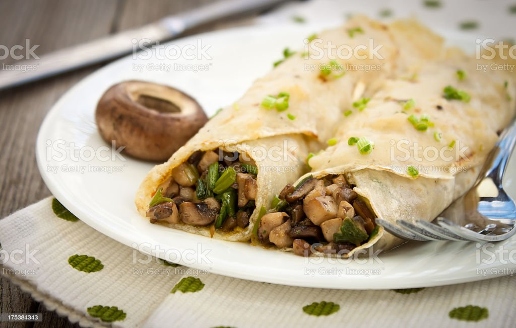 Two crepes filled with savory herbs and mushrooms stock photo
