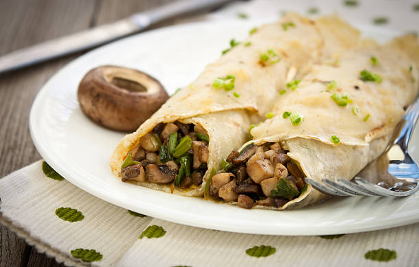 two crepes filled with savory herbs and mushrooms - gezout stockfoto's en -beelden