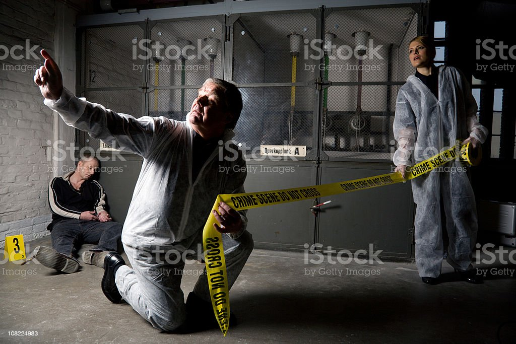 Two Crime Scene Investigators wiith Police Tape royalty-free stock photo