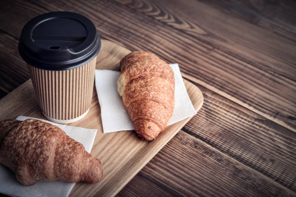 Two croissants and coffee-to-go Two croissants and coffee-to-go on tray over wooden background pastry dough stock pictures, royalty-free photos & images