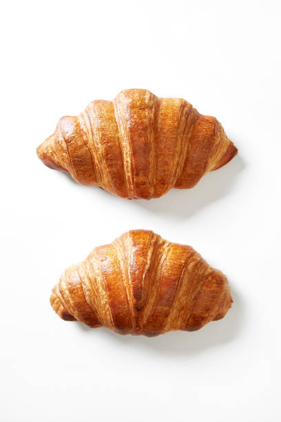 Two croissants isolated on a white background viewed from above. Top view. Two croissants isolated on a white background viewed from above. Top view. croissant stock pictures, royalty-free photos & images