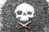 istock Two crossed bone-shaped smoking cigarettes lie next to a skull formed by tobacco ash. Concept: smoking is harmful, cigarettes are dangerous. 1187856468