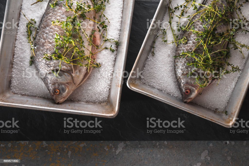 Two  crucians with salt and rosemary in  baking dishes horizontal 免版稅 stock photo