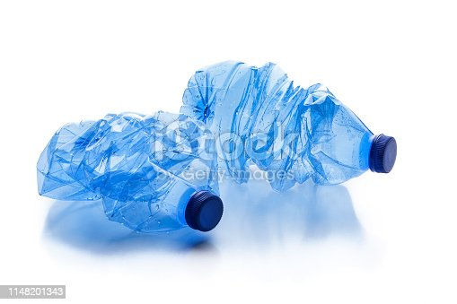 Environmental conservation and recycling concepts: two crushed bluish plastic water bottles isolated on white background. Useful copy space available for text and/or logo. Predominant colors are blue and white. High key DSRL studio photo taken with Canon EOS 5D Mk II and Canon EF 70-200mm f/2.8L IS II USM Telephoto Zoom Lens