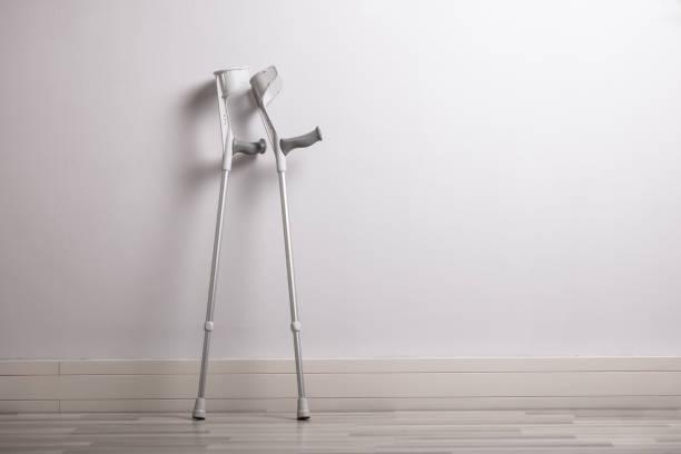 コンクリート壁にもたれる2つの松葉杖 - 杖 ストックフォトと画像