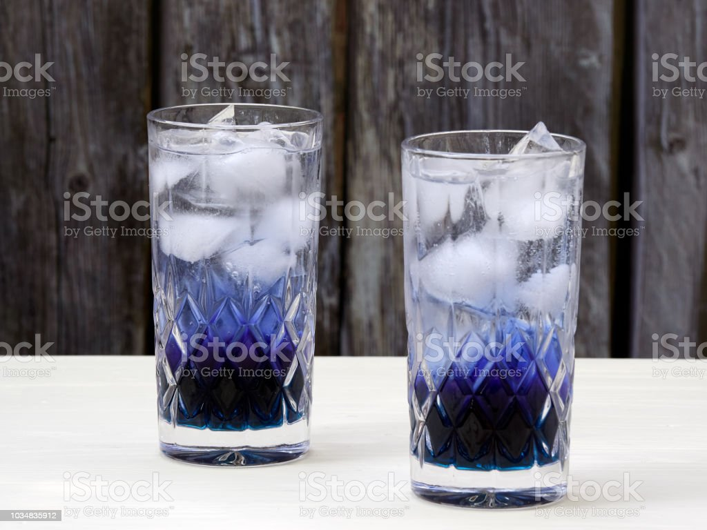 Two crystal glasses filled with layered butterfly pea flowers soda stock photo