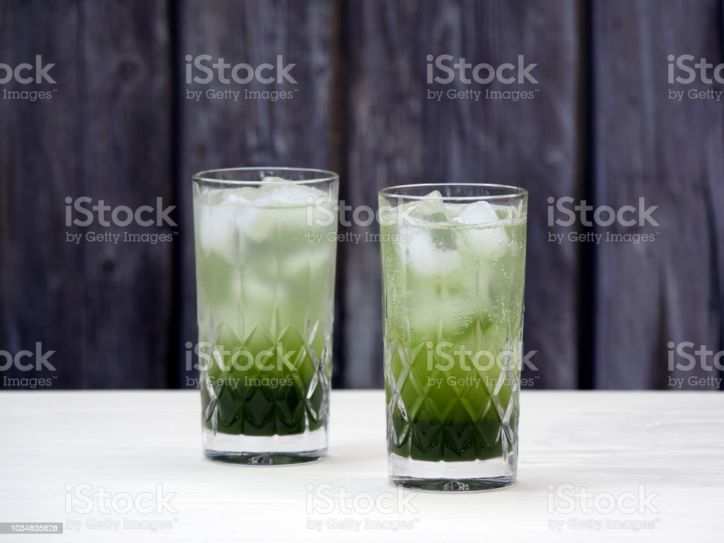 Two crystal glasses filled with layered matcha soda stock photo