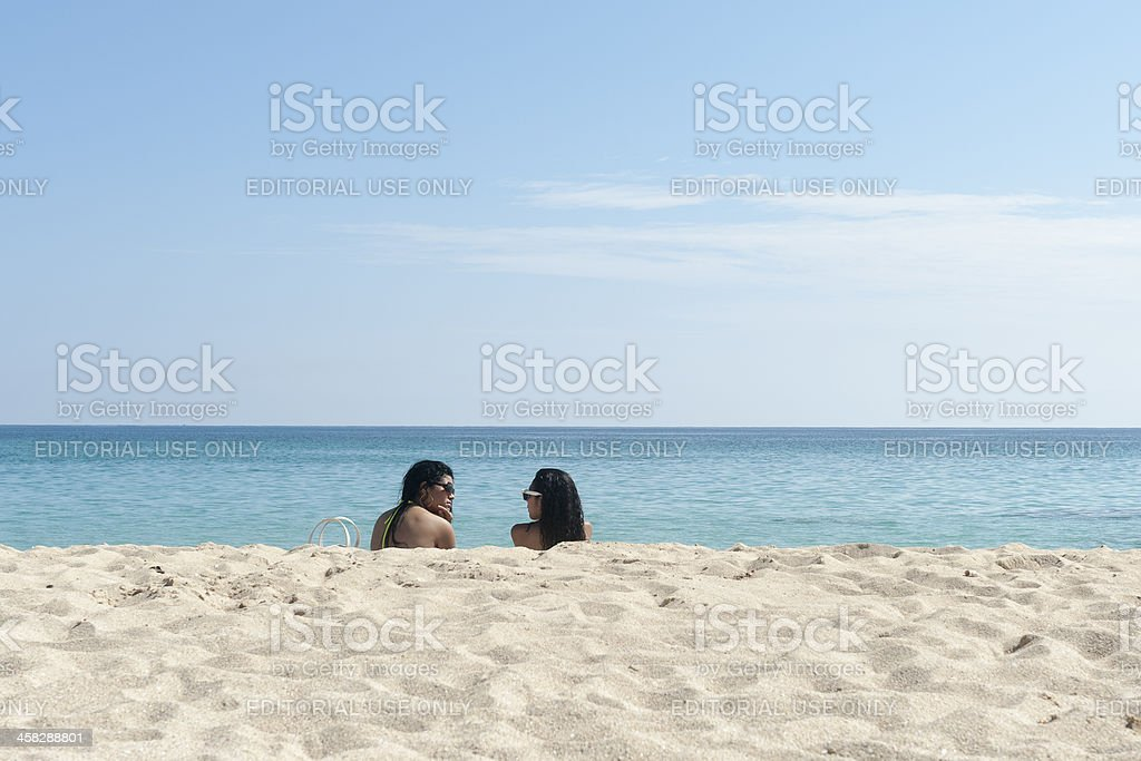 two cuban ladies are sitting on the beach royalty-free stock photo