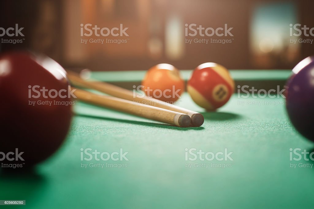 Two cues and spheres on a billiard table. - foto de acervo