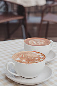 A two cup of cappuccino or latte with a pattern on the table with a checkered tablecloth. The table is located on the terrace of a cozy cafe.