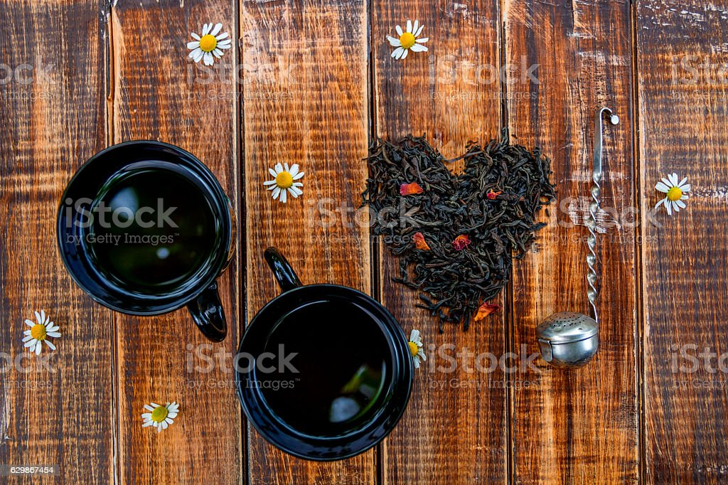 Two cup of tea near dry leaves black stock photo